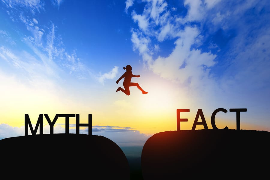 Woman jumps through the gap between Myth to Fact on sunset.
